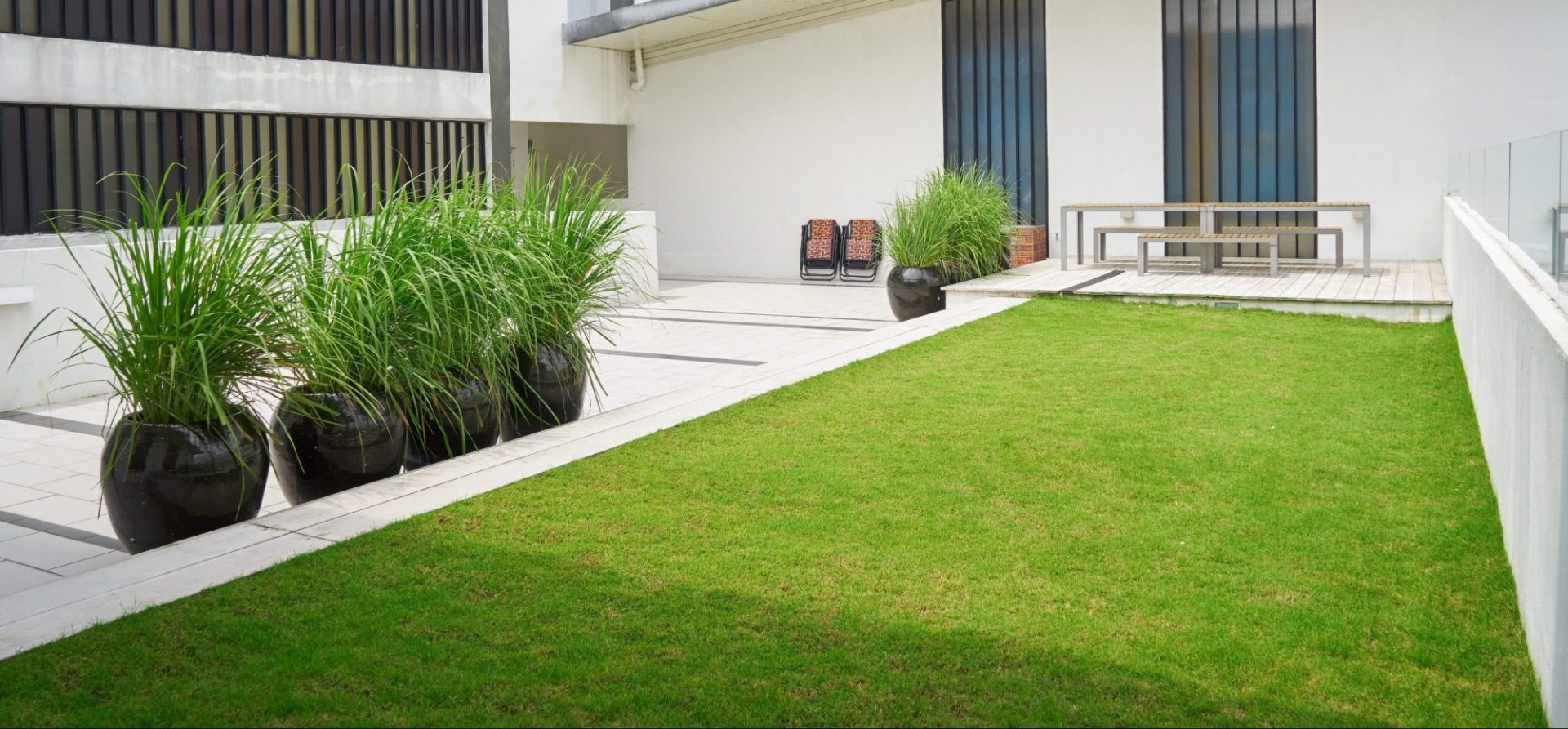 Hardscape patio at industrial facility with potted grasses and turf.